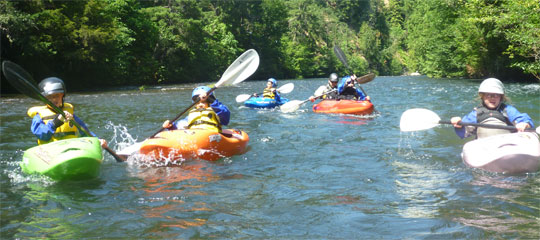 Kids head down the Lower White Salmon River during a summer kids kayak course.