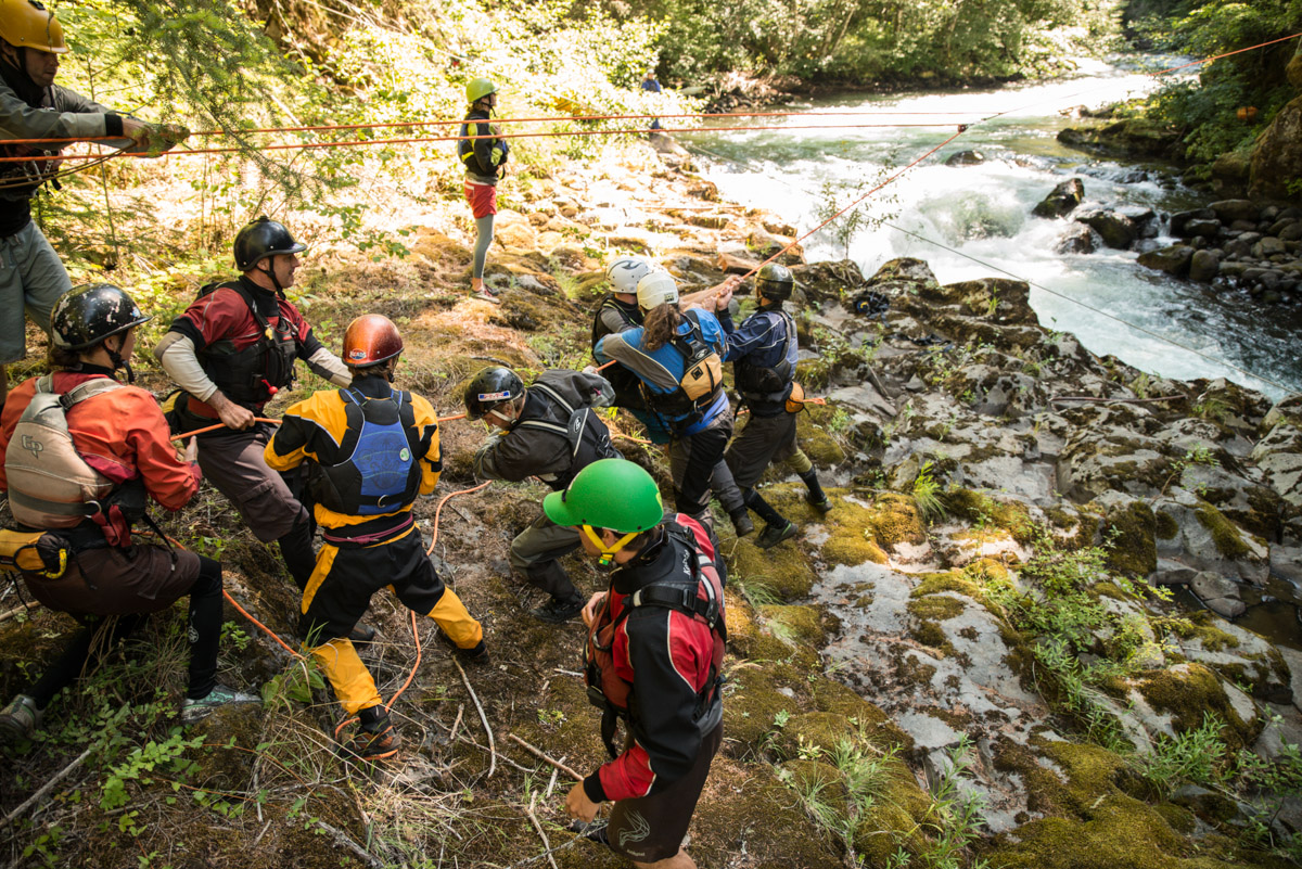 A team of Wet Planet guides works to safely reposition a log on the White Salmon River.